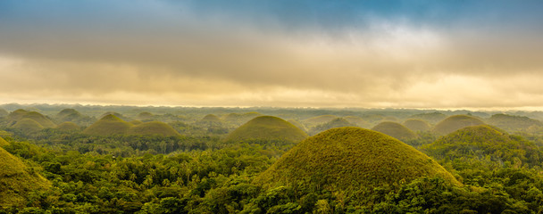 Scenic view of the UNESCO site of Chocolate Hills in Bohol, Philippines, with clouds and sun