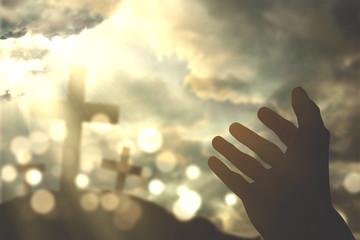 Human hands praying with cross symbol