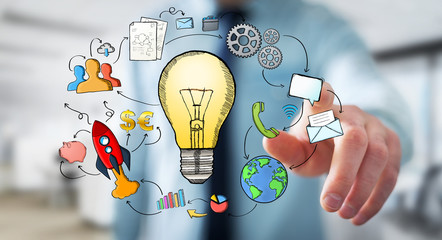 Businessman touching hand drawn lightbulb and multimedia icons