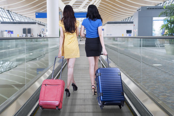 Two women carrying suitcases for traveling