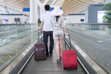 Young couple carrying suitcases for traveling