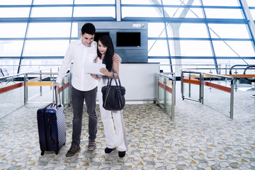 Young couple checking flight information on tablet