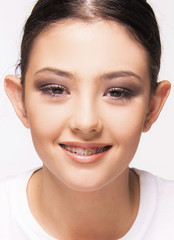 girl with brace smiling on white