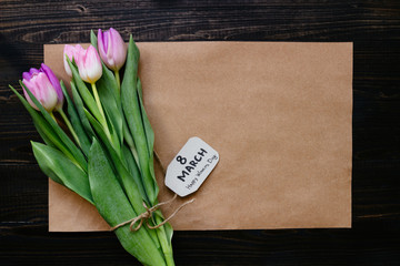 Women's day. Bouquet of beautiful fresh tulips with paper on the wooden background