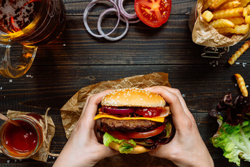Fototapeta Hands holding fresh delicious burgers with french fries, sauce and beer on the wooden table top view obraz