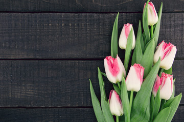 Bouquet of Tulips on dark rustic wooden background with copy space for message. Spring flowers. Greeting card for Valentine's Day, Woman's Day and Mother's Day holidays. Top view