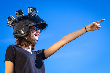 une jeune femme avec quatre caméras de sport sur la tête ,collées sur un casque indique une direction avec son bras
