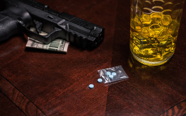 drugs, alcohol, guns, and money laid out on a table
