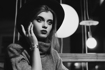 Monochrome indoor portrait of young beautiful fashionable woman touching her face, looking forward. Girl sitting in cafeteria. Model wearing stylish turtleneck and wide-brimmed hat. Female fashion