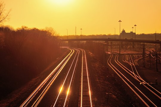 The setting sun reflecting off Burlington Northern Santa Fe and Metra railroad tracks in Aurora, Illinois.
