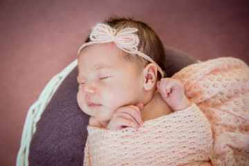 Newborn baby sleeps in a basket in a pink blanket