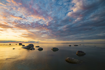 Baltic sea at beautiful sunrise,stony beach after storm