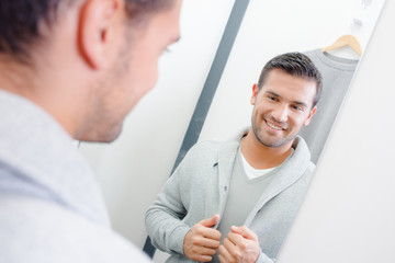 Man trying on jacket, looking at reflection in mirror
