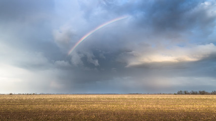 rainbow on an abandoned field / bright spring storm clouds Photo