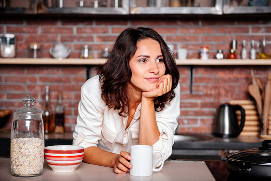 Young happy woman drinking coffee on the kitchen