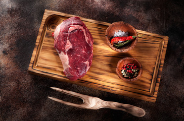 Wall Mural - Raw fresh meat Ribeye Steak on a brown rusty background top view