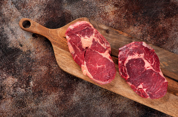 Wall Mural - Raw ribeye steak on a wooden board, top view