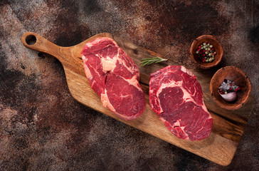 Wall Mural - Raw ribeye steak on a brown rusty background, top view,