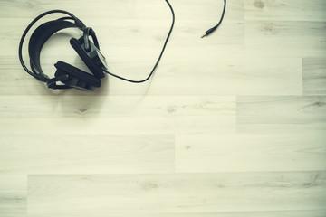black headphones on white, wooden background