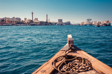 Panoramic view from traditional water taxi boats in Dubai, UAE. Creek gulf and Deira area. United Arab Emirates famous tourist destination. Creative color post processing.