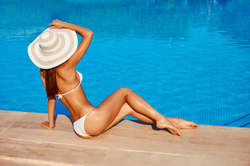Portrait of beautiful tanned sporty slim woman relaxing in swimming pool spa. Creative white hat and bikini. Hot summer day and bright sunny light.
