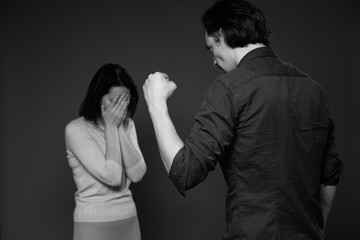 Family abuse - man threatening woman showing the fist, she is scared, her face is hidden in the palms, black and white