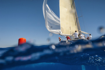 Sailing boat with spinnaker on windward mark - red buoy. Waterline view.