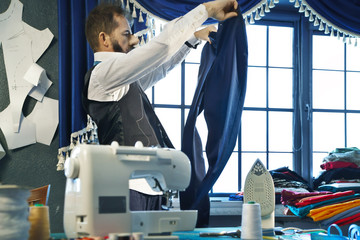 Tailor sews a trousers