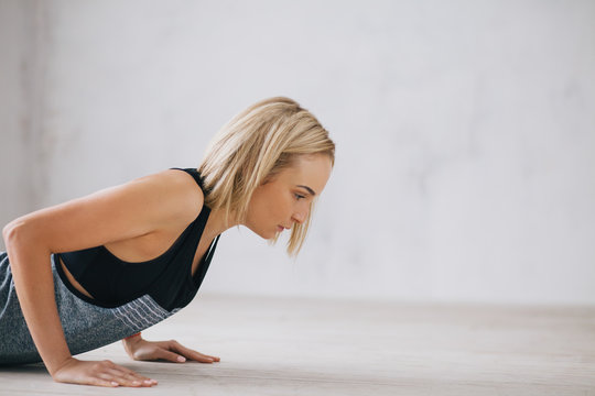 Closeup of young happy attractive woman doing push ups or press ups exercise