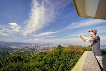 Tourist attraction. Traveler taking photo with smartphone camera on the view point enjoying sea, city and sky.