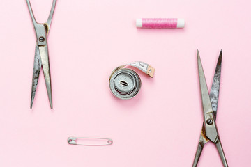 Sewing equipment for fabric with tape measure, scissors, string and needle on pink