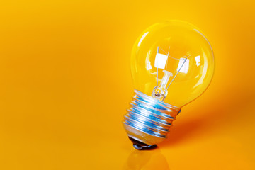 Clear Light Bulb with Yellow Background