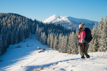 Happy young woman with a backpack standing on snow  and looking into the mountains