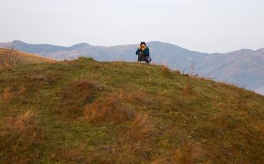 female photographer at sunrise, misty mountains