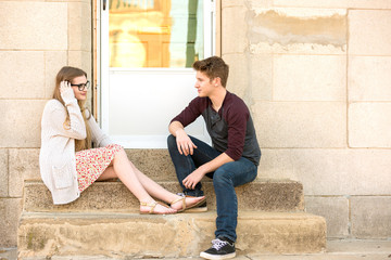 Young couple talking on the steps.