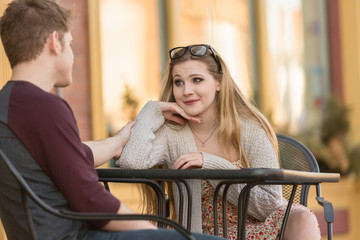 Young couple sitting at an outside table talking, camera focus on the girl.