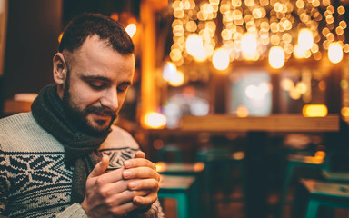 portrait of handsome guy is holding coffee cup