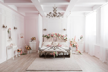wrought iron bed in the gentle light room. spring flower decoration.