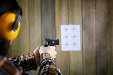 man with put on protective goggles and ear training in pistol shooting