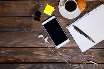 White mobile phone on wooden wooden background with headphones, cup of coffee, croissant and Stationery appliances