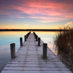 Cichy jezioro przy wschodem słońca, drewniany molo zakrywający z hoarfrost