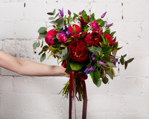 Creative bouquet of flowers at arm's length, beautiful flowers as a gift beloved.