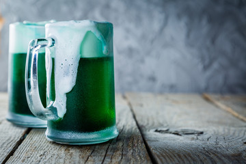 Green beer in mugs on rustic wood background