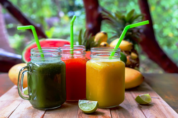 Fresh juices smoothie with tropical fruits banana, pineapple, lime melon, mango on wooden table. Top view. Healthy style raw vegan concept.