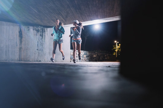 Two young women jogging at night in city