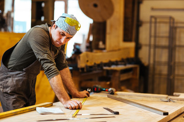 Repairman or cabinetmaker looking at sketch of new detail