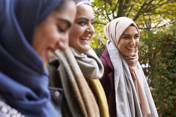 Three smiling woman wearing hijabs