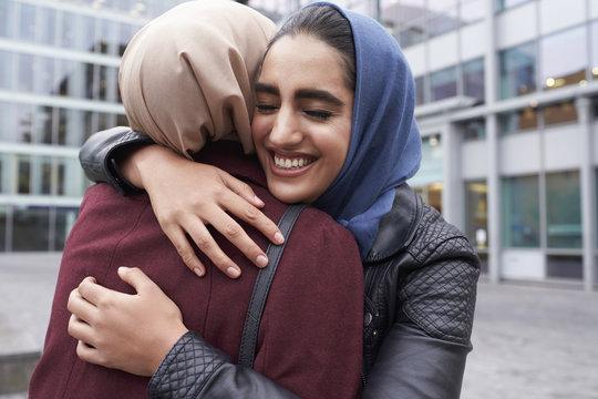 Two British Muslim Women Friends Meeting Outside Office