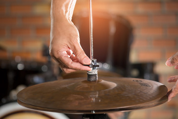 Hands setting hihat of  drum kit.Drummer adjusting hihat for a proper sound and feeling in live concert.