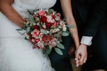 bride and groom holding hands + bouquet